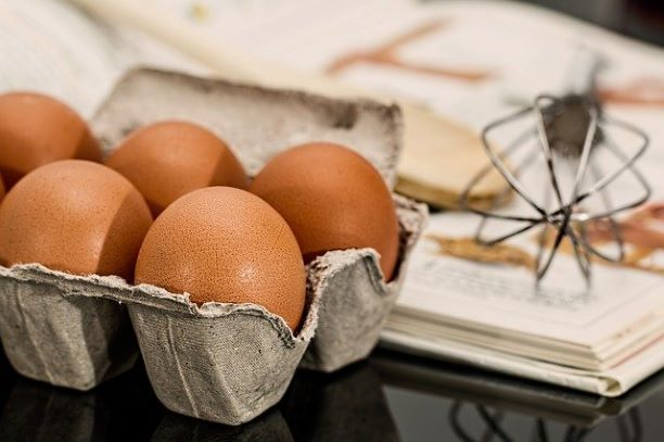 eggs in a carton with whisk in background