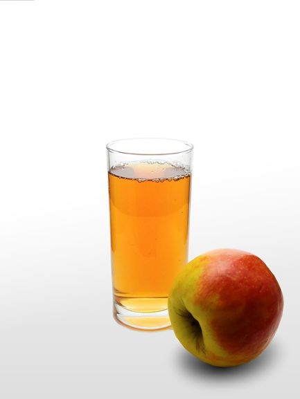 a glass of apple juice with a whole apple next to the glass