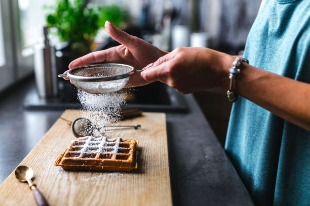 woman-pouring-sugar-over-her-waffle