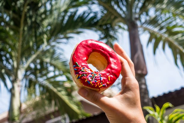 holding-donut-near-palm-trees