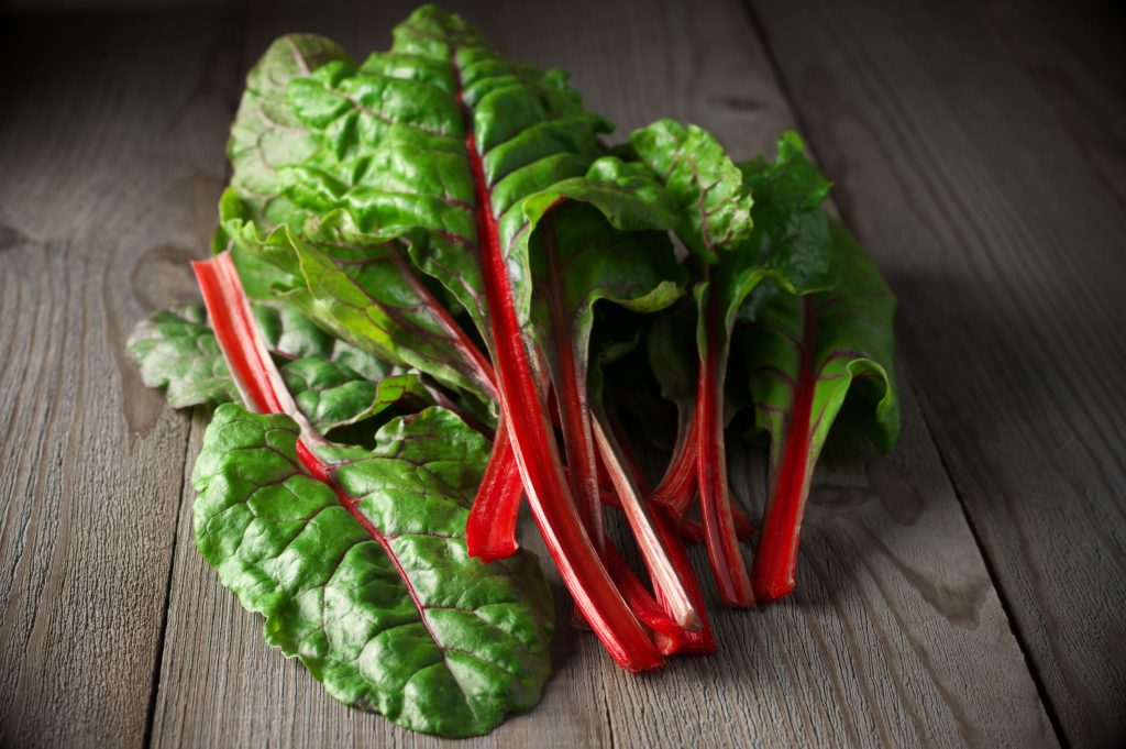 fresh swiss chard on wooden table