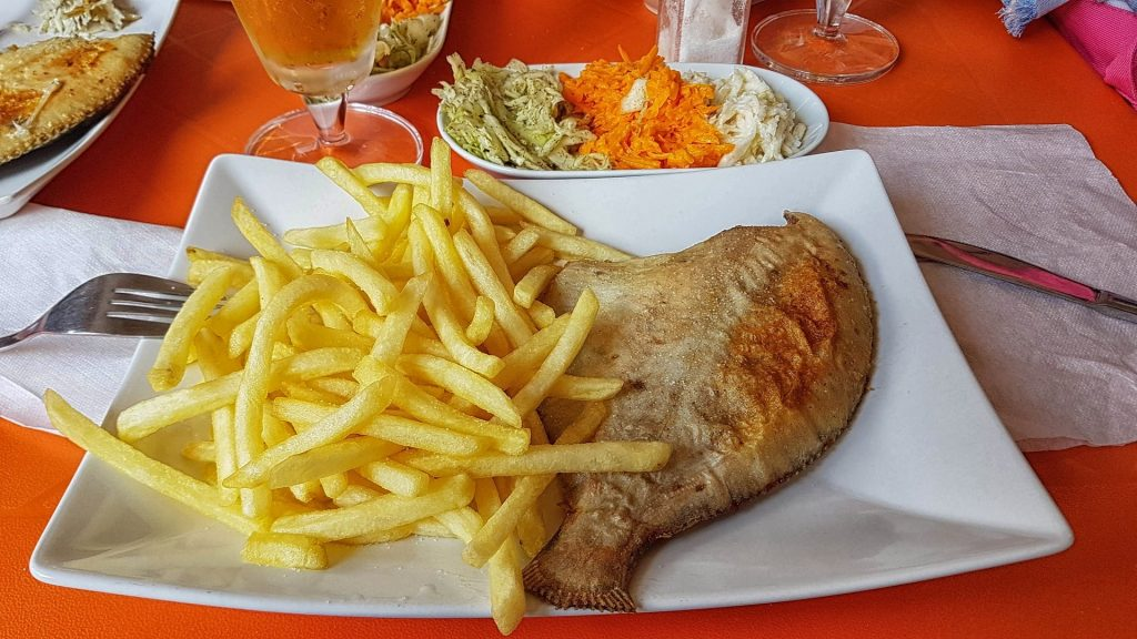 plate with french fries and cooked flounder