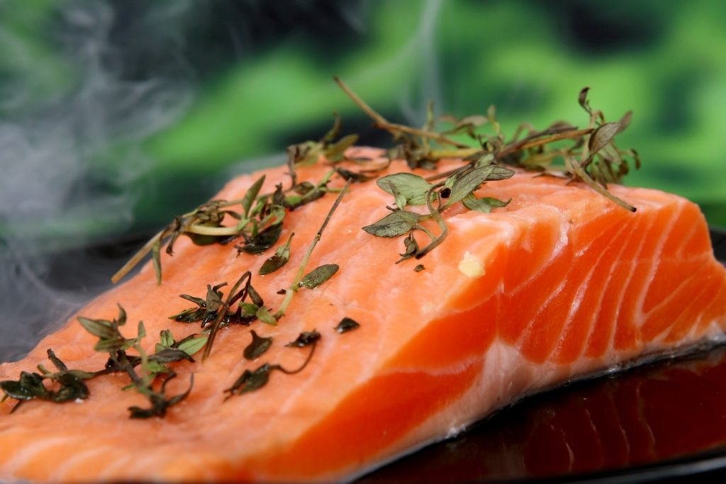 a plate containing steaming salmon that has been cooked