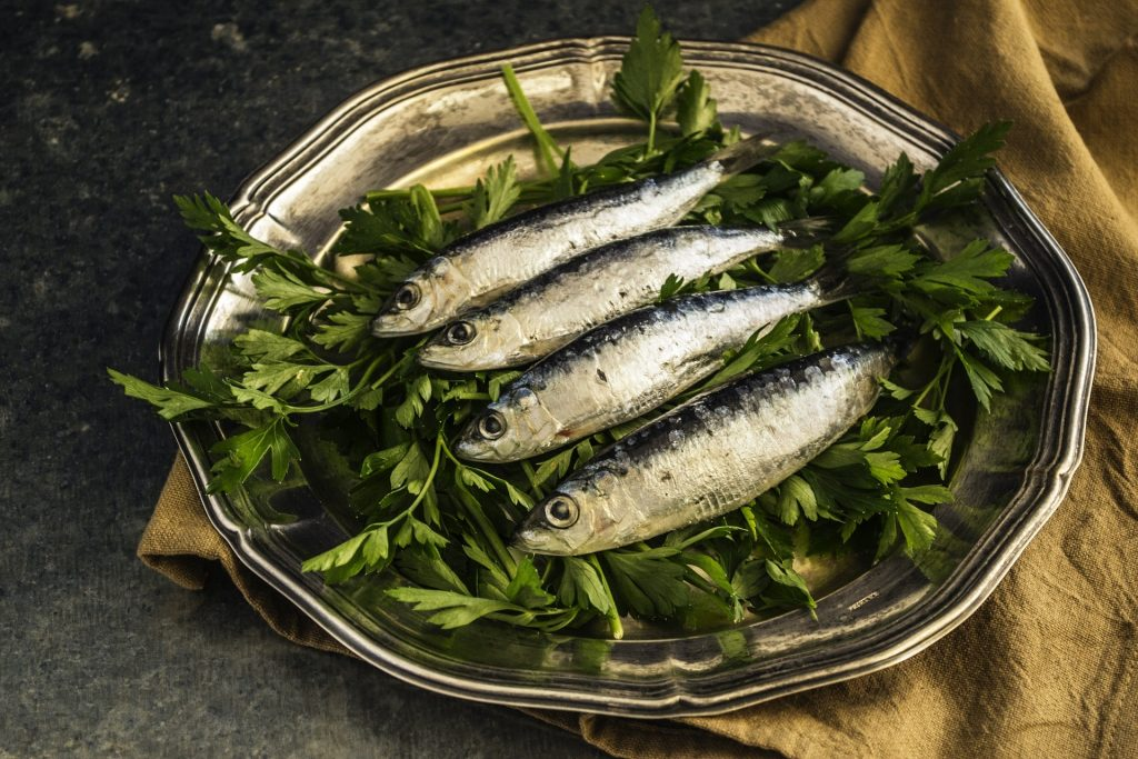 plate with green, leafy vegetables, and a bunch of sardines placed on the top